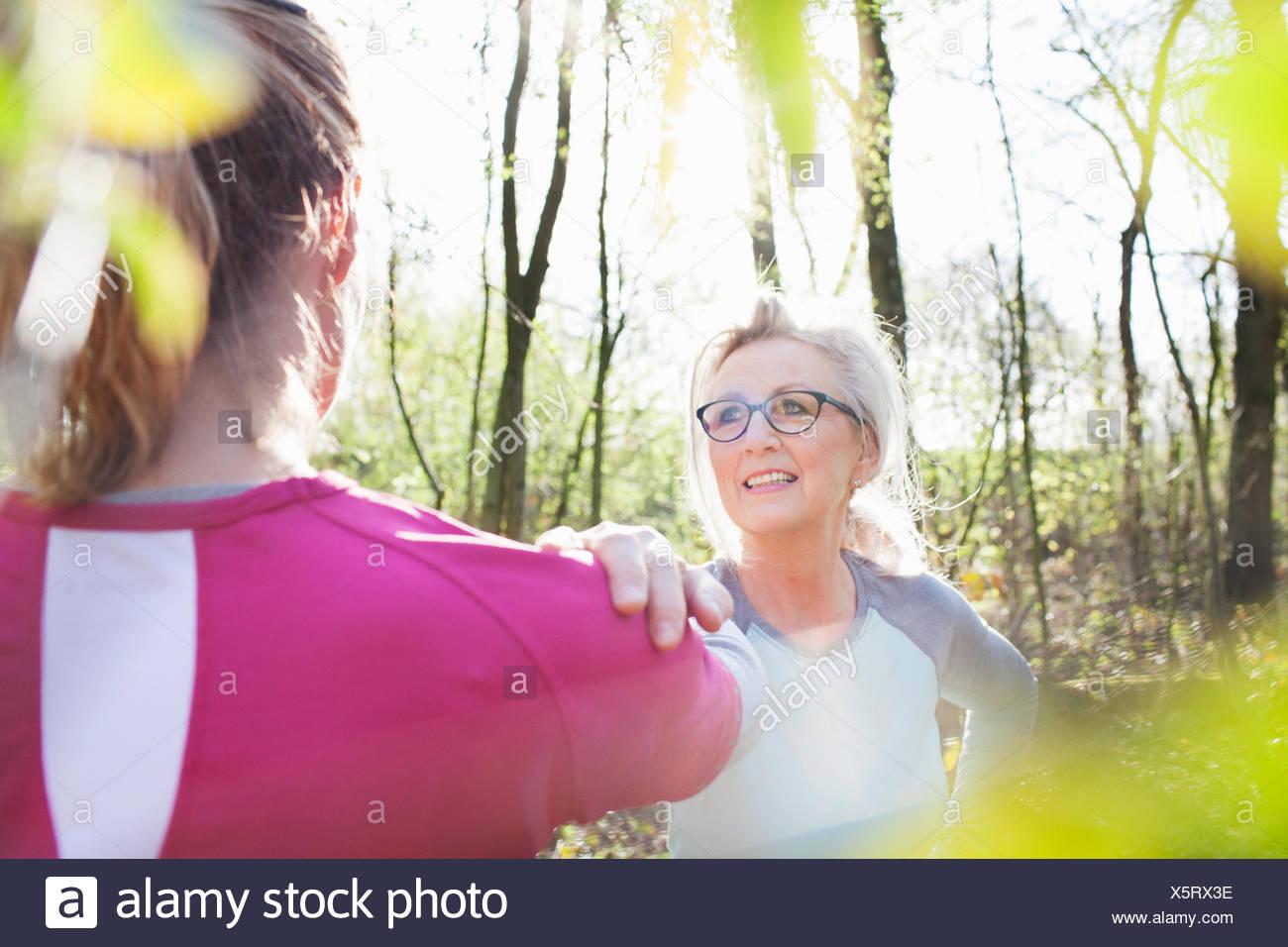 Les femmes en forêt, main sur chaque autres épaules stretching Photo Stock