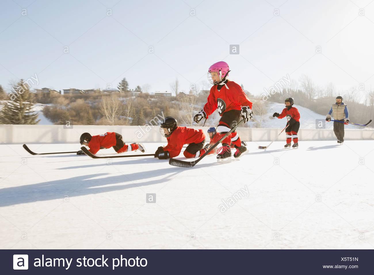 L'équipe de hockey sur glace d'effectuer des exercices de formation sur une patinoire extérieure Photo Stock