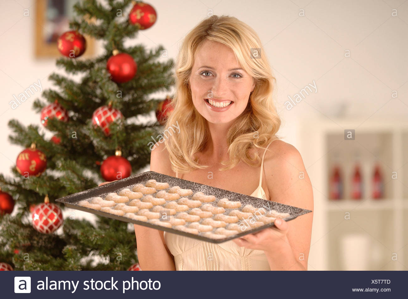 Femme blonde, 20-30, portant une robe de soirée tout en tenant une plaque de cuisson avec des biscuits de Noël en face d'un arbre de Noël Photo Stock