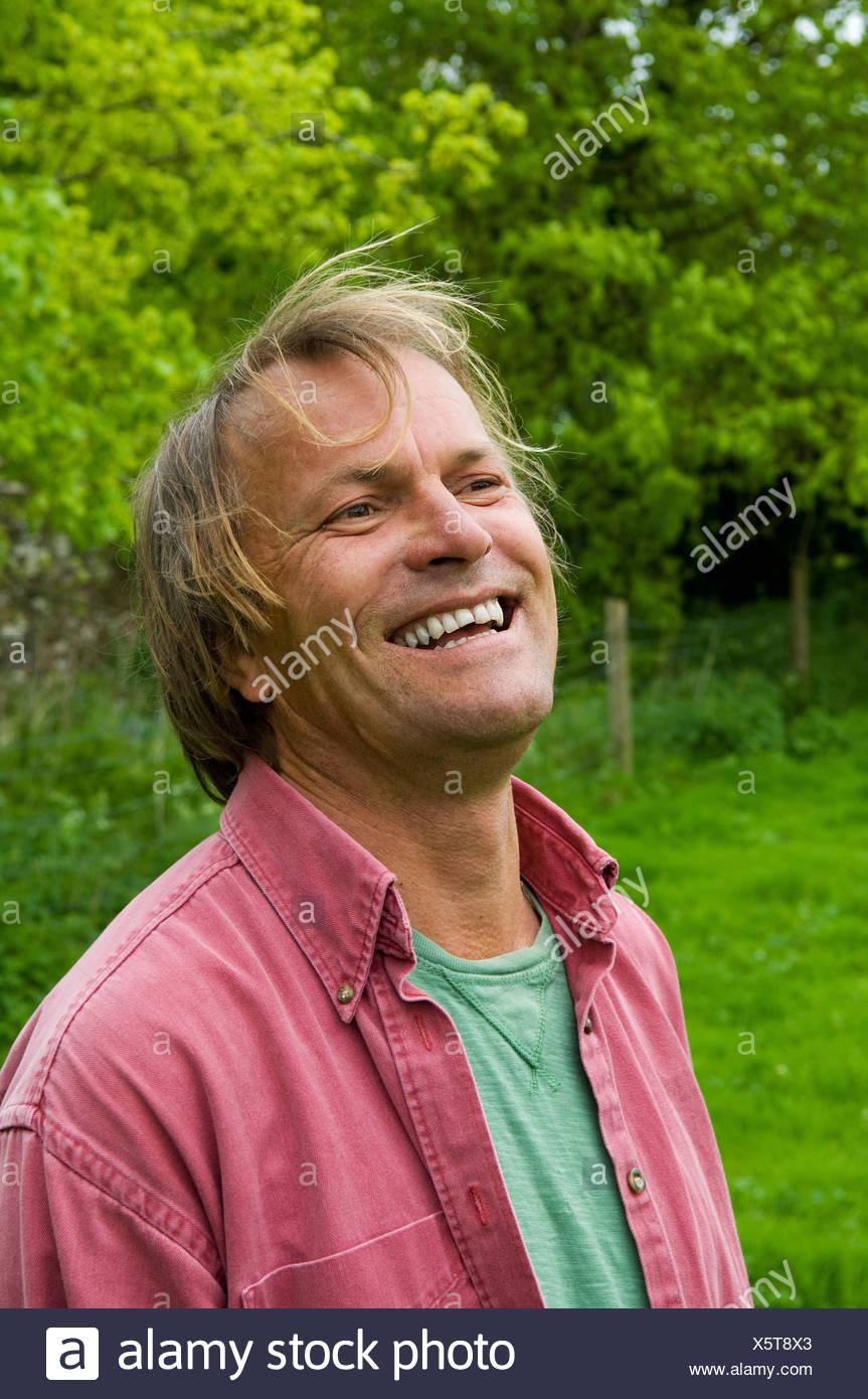 Un homme mûr dans les tenues avec des cheveux blonds, souriant largement. Photo Stock