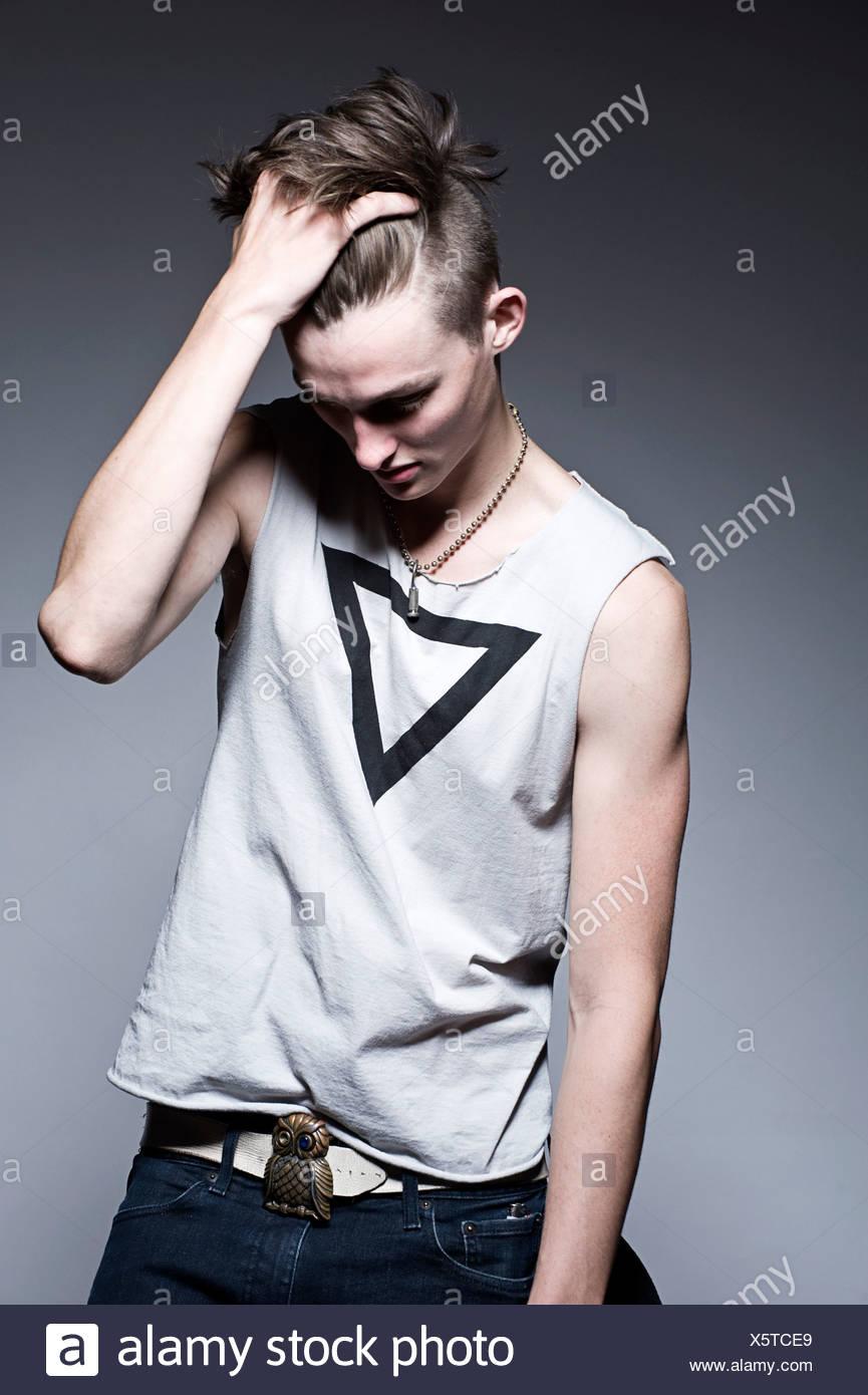 Jeune homme à la main dans les cheveux à la recherche vers le bas, studio shot Photo Stock