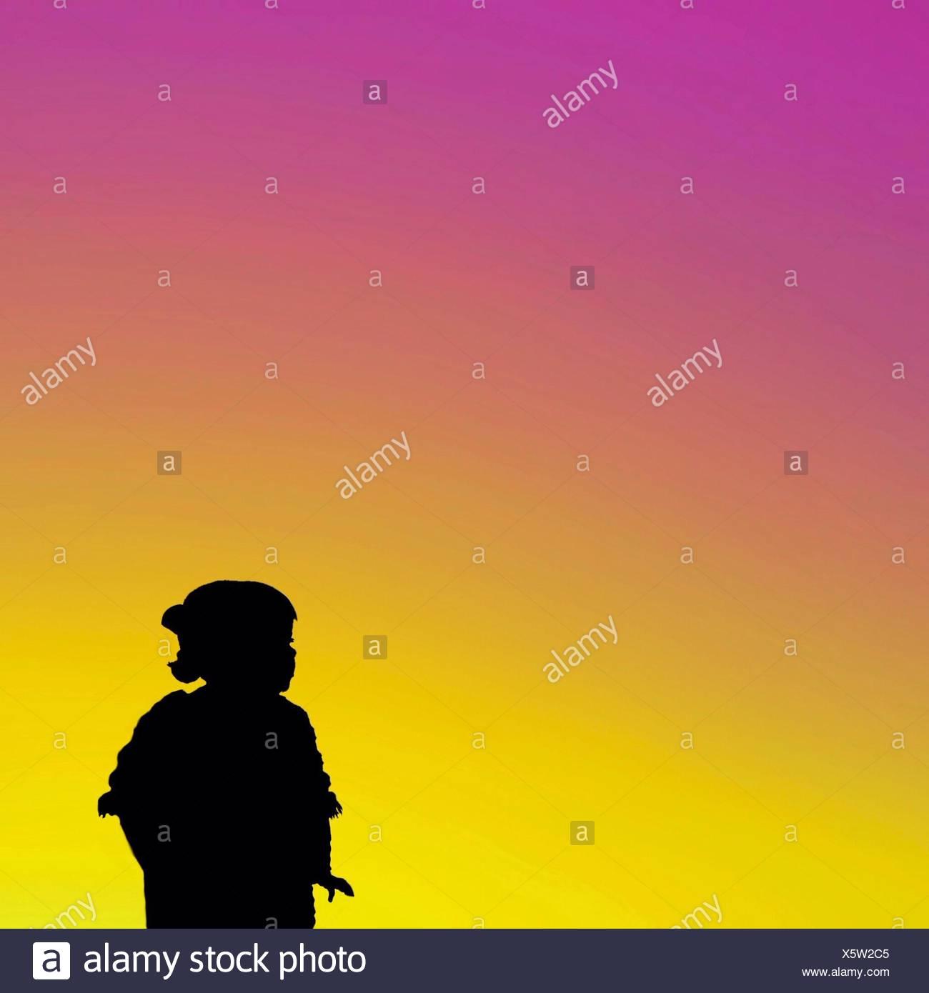 Fille Silhouette contre ciel dramatique Photo Stock
