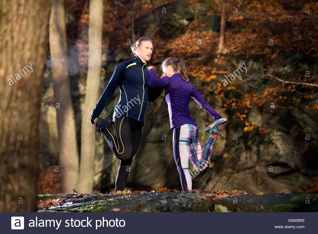 Couple in forest appuyé contre chaque autre jambe soulevée maintenant étirement pied Photo Stock