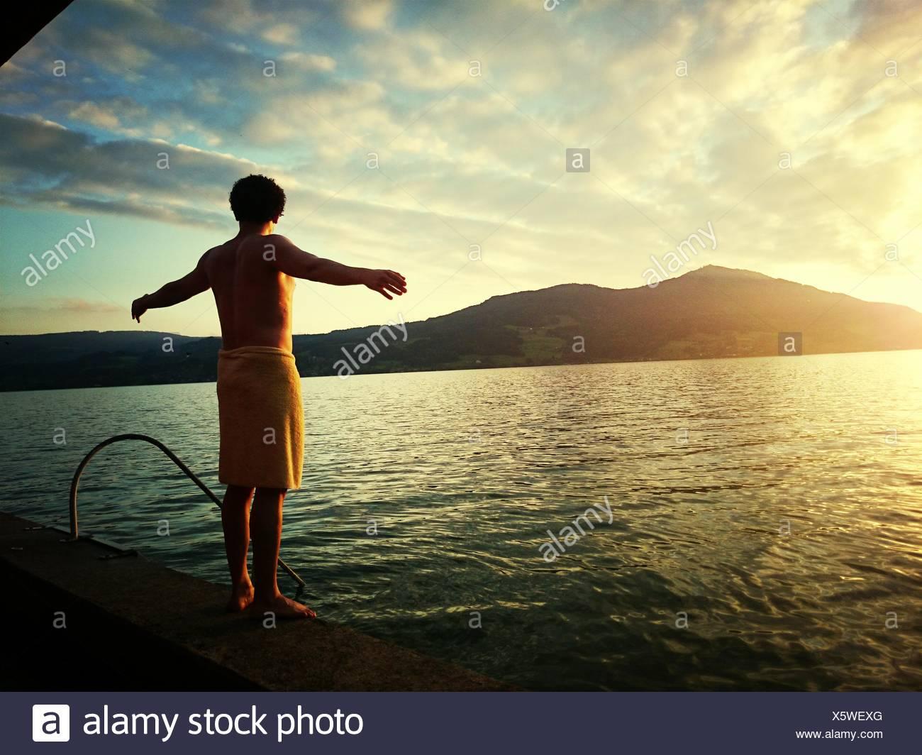 Vue arrière de Man With Arms Outstretched Standing sur mur de retenue en mer Photo Stock