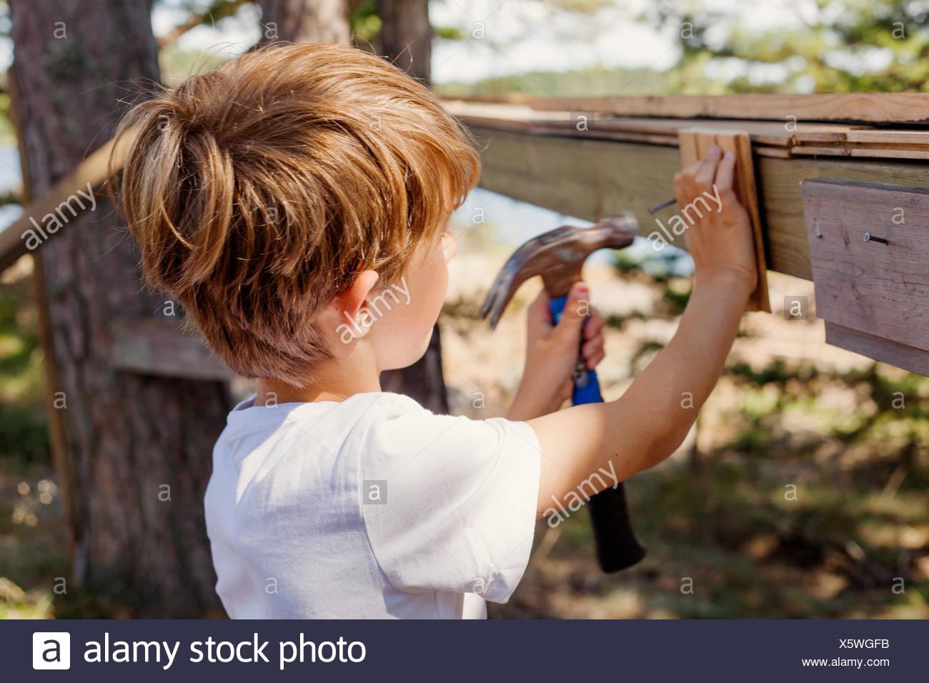 La Suède, l'Uppland, Runmaro Barrskar, garçon, (4-5) pounding hammer Photo Stock