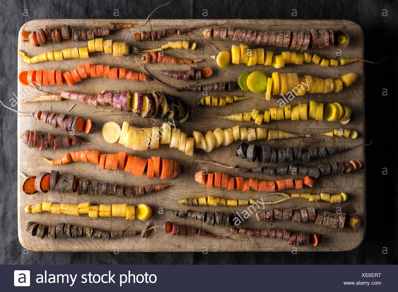 Un tableau de carottes arc-en-ciel dans beaucoup de formes et de couleurs, toutes finement hachés sur un billot de bois usés. Photo Stock