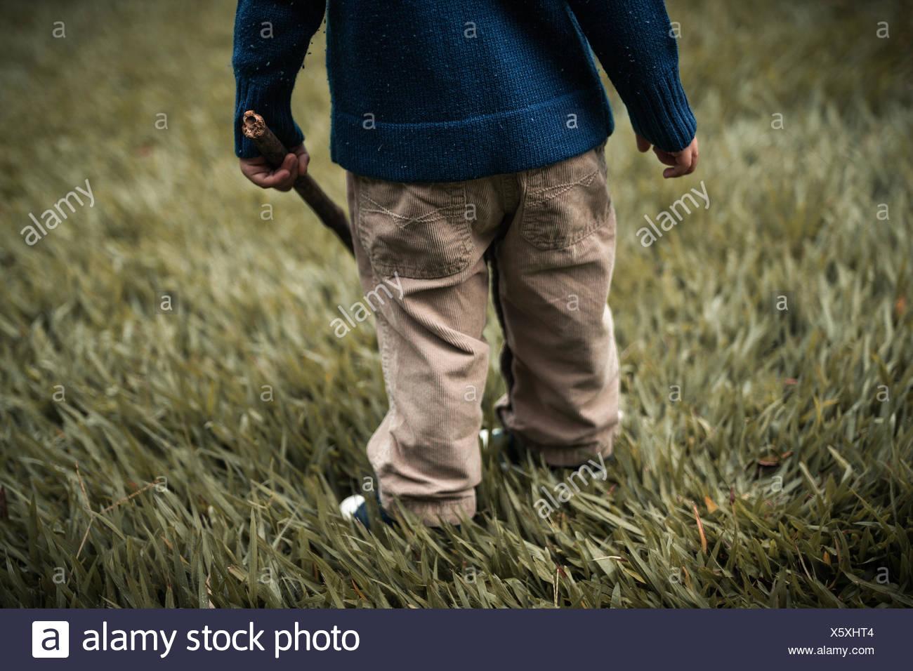 La section d'un enfant en bas standing in field tenant un bâton en bois Photo Stock