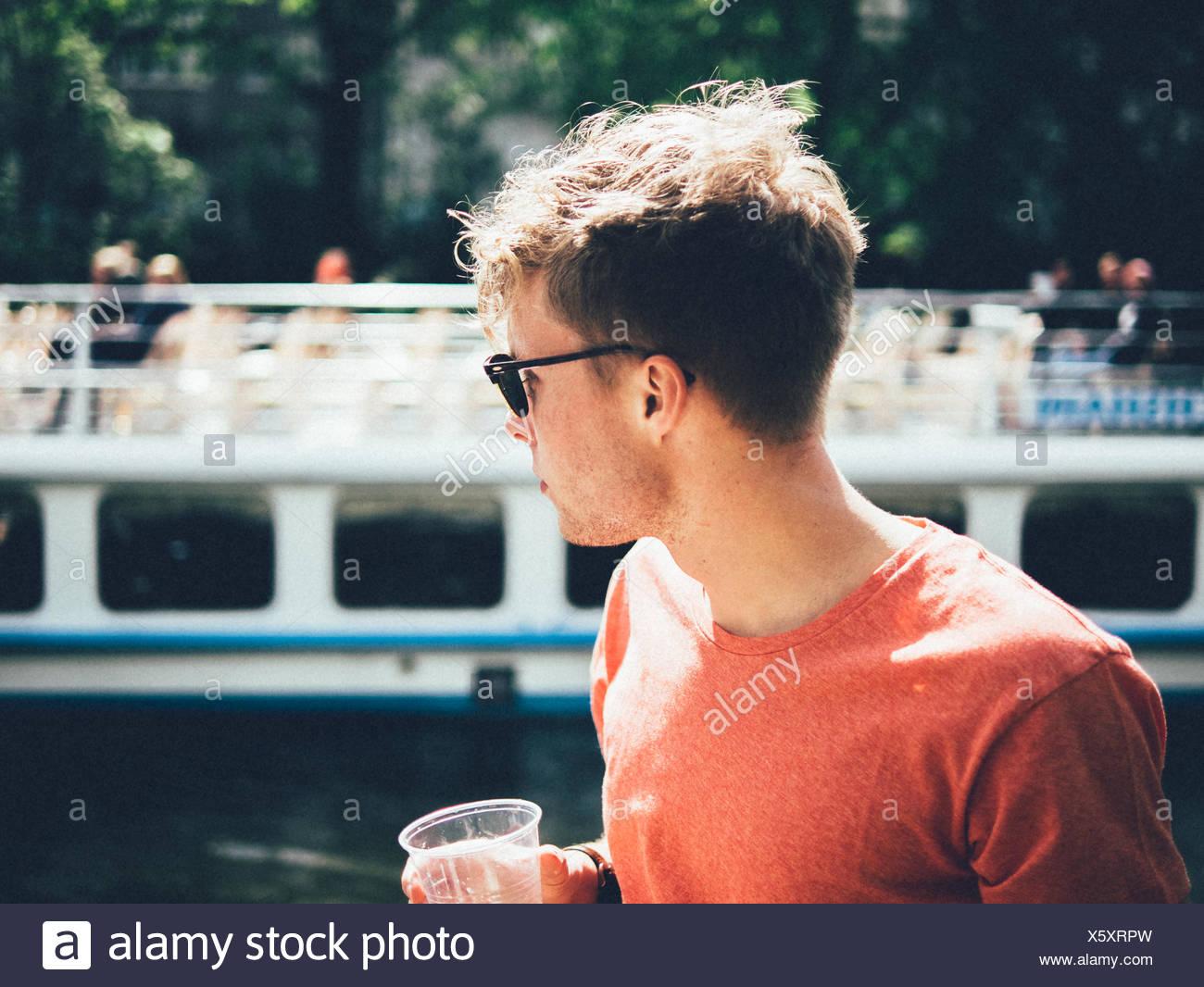 L'homme portant des lunettes de soleil en position debout par canal Photo Stock