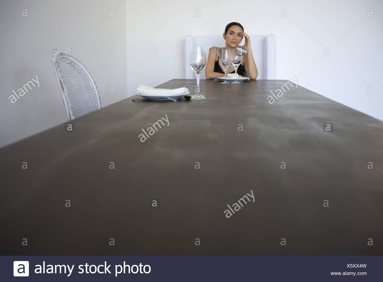 Femme assise seule à la table pour deux, holding head Banque D'Images
