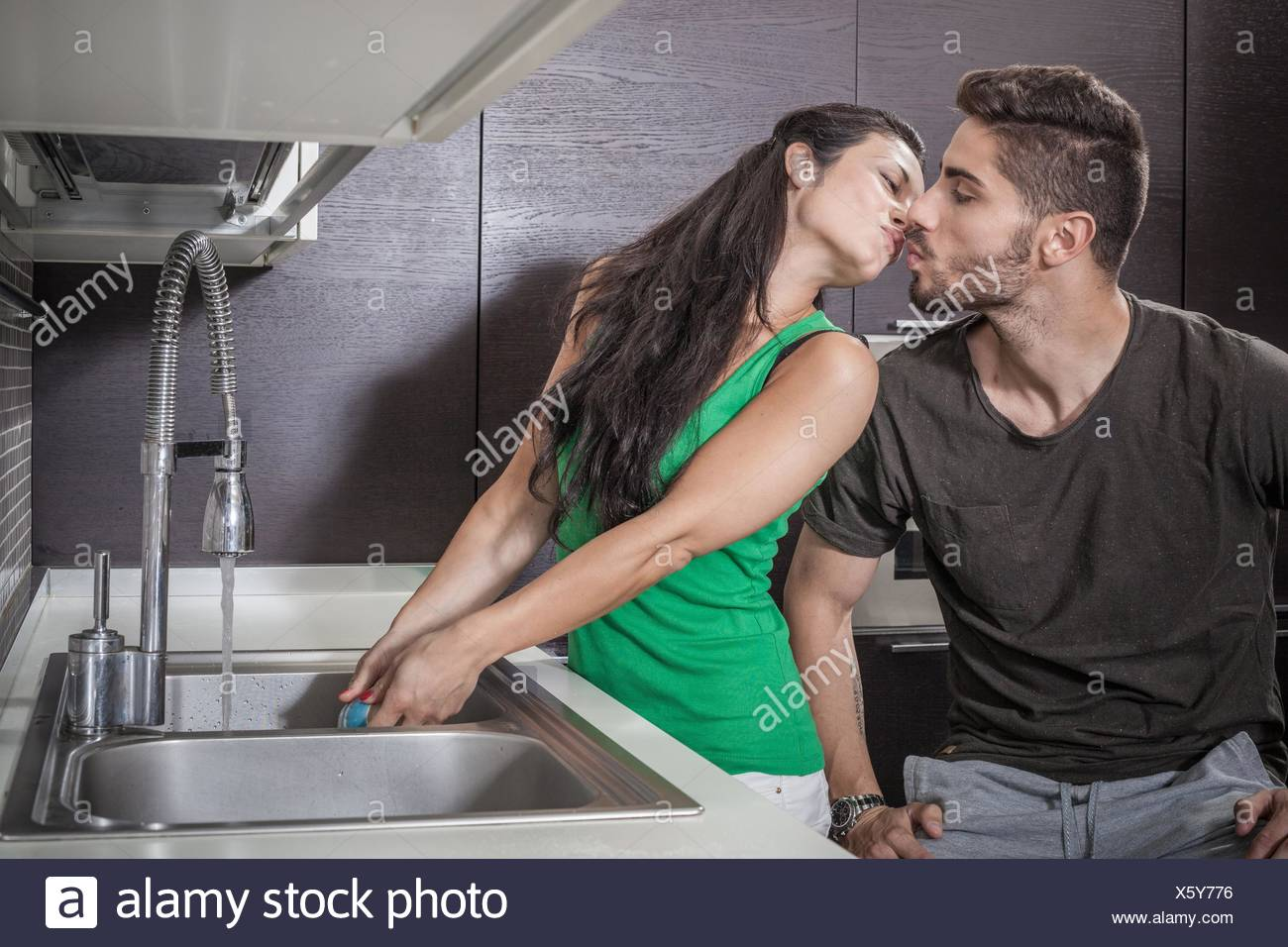 Young woman washing up alors que les baisers petit ami Photo Stock