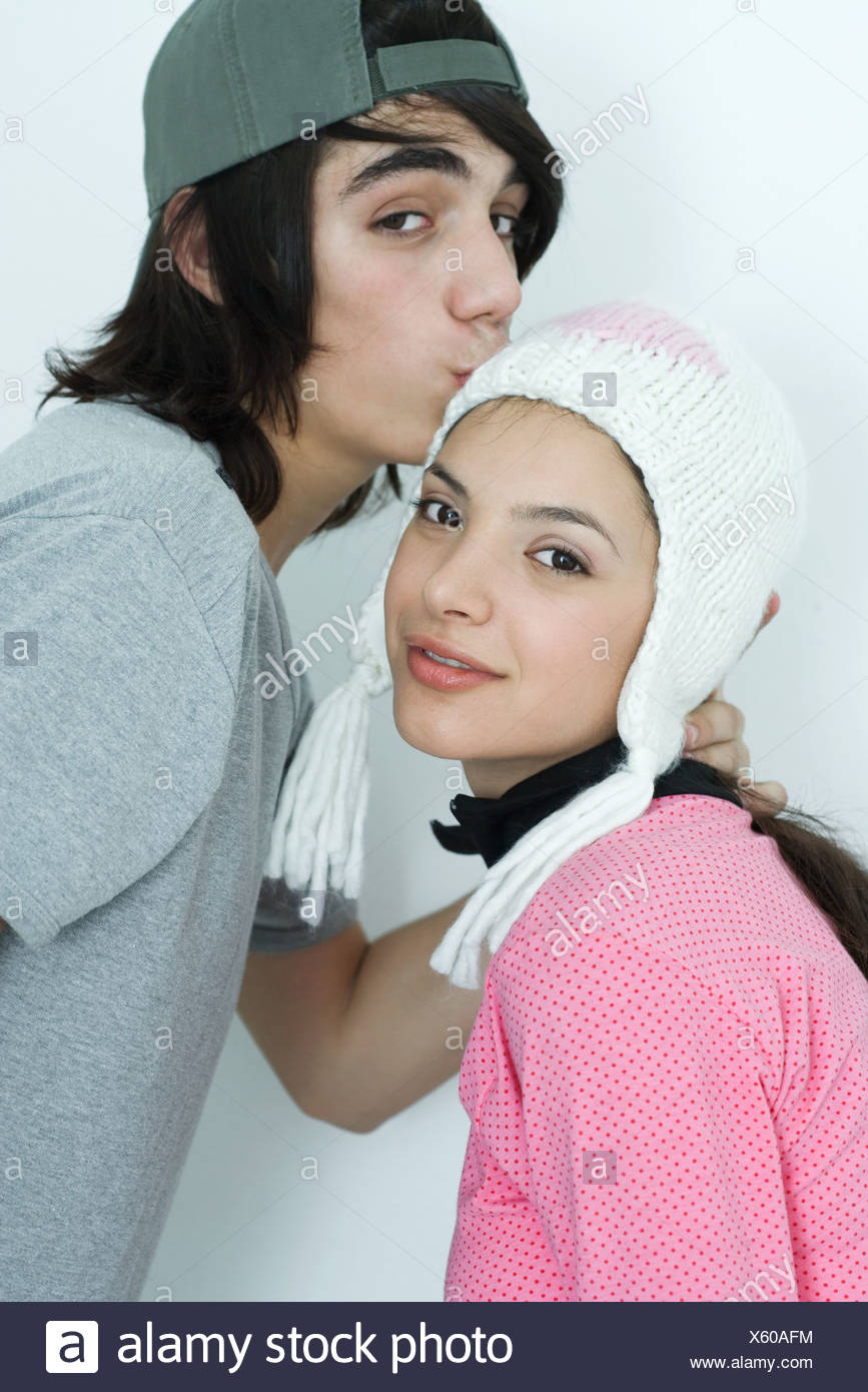 Young couple wearing hats, teen boy kissing petite amie sur tête, portrait