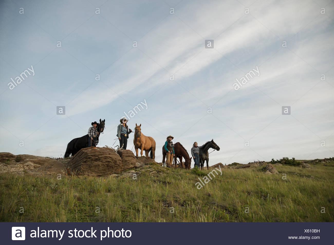 Femme debout avec des éleveurs de chevaux sur une colline à distance Photo Stock