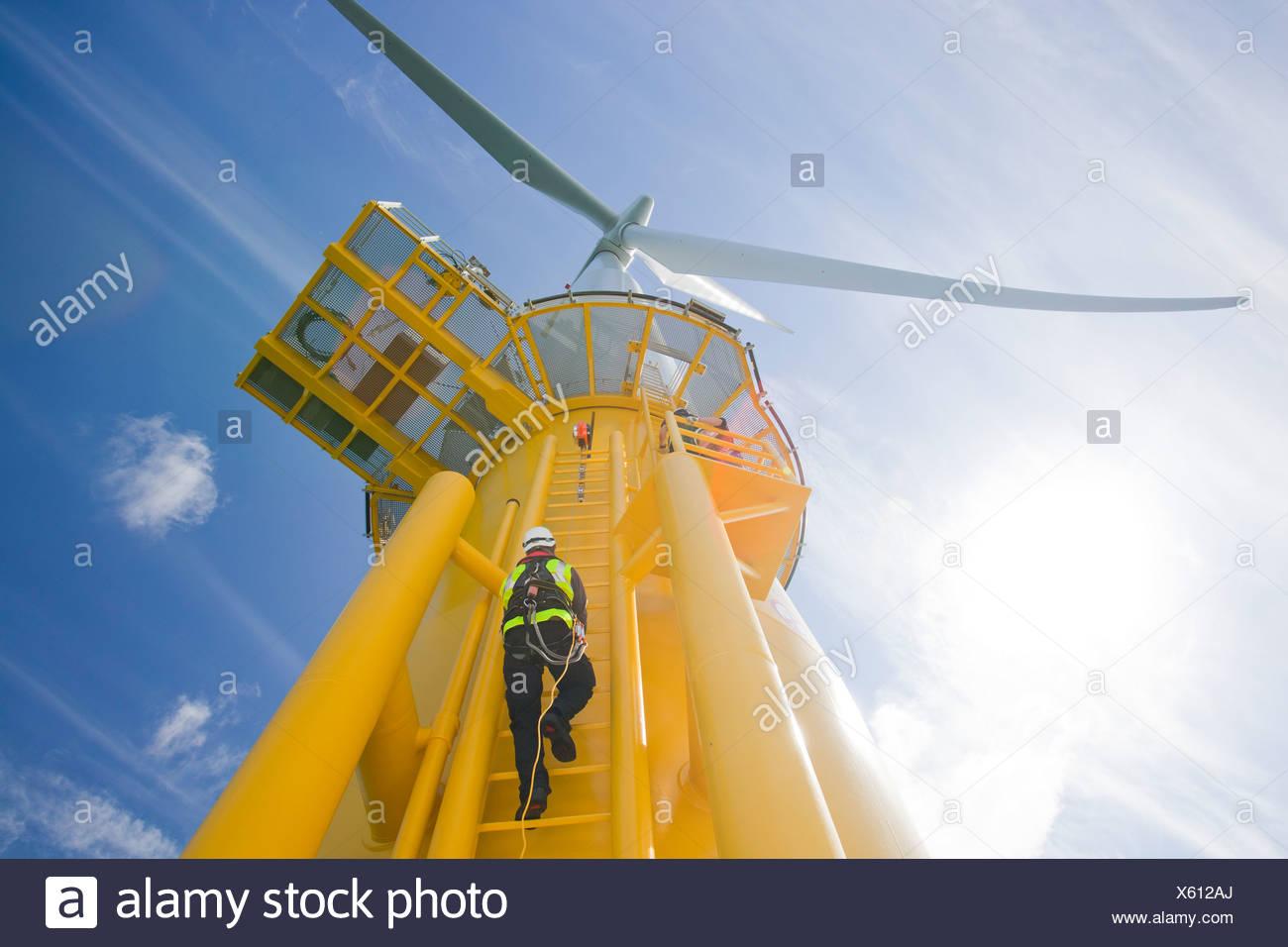 Un travailleur l'ascension d'une éolienne à l'éolien offshore Walney. Photo Stock