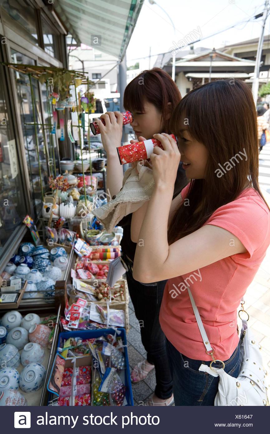 Deux jeunes femmes à l'intermédiaire de kaleidoscope Photo Stock