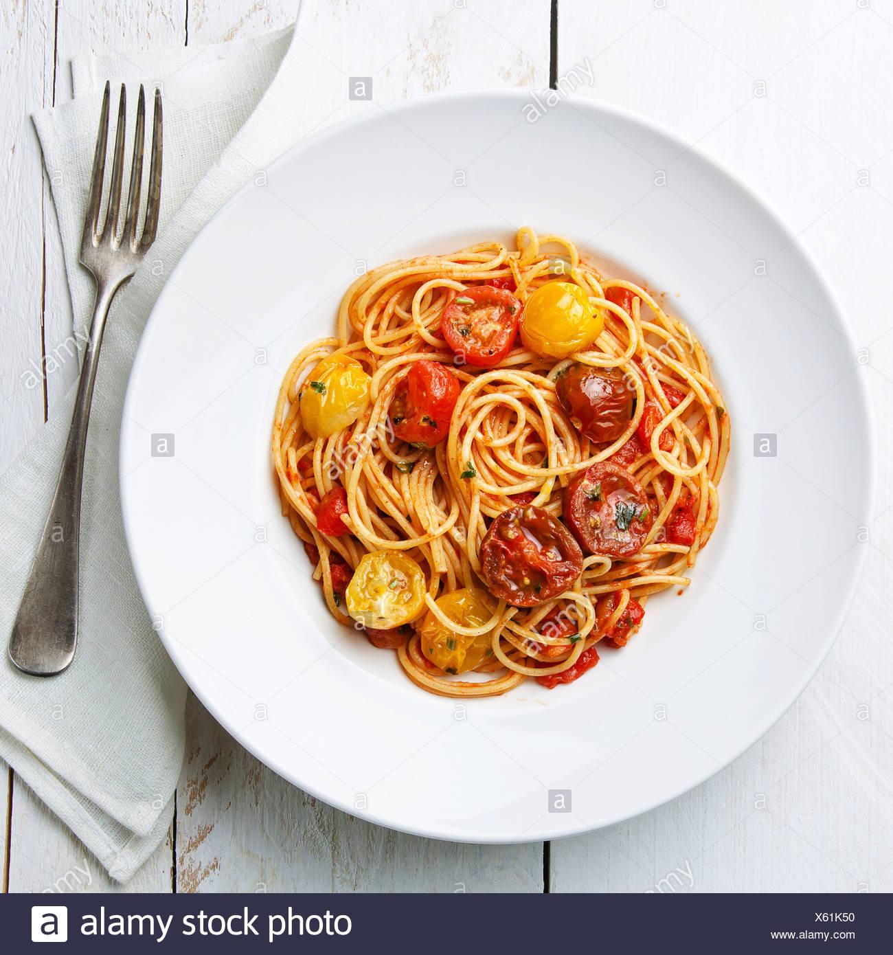 Spaghetti à la sauce tomate sur fond de bois blanc Photo Stock