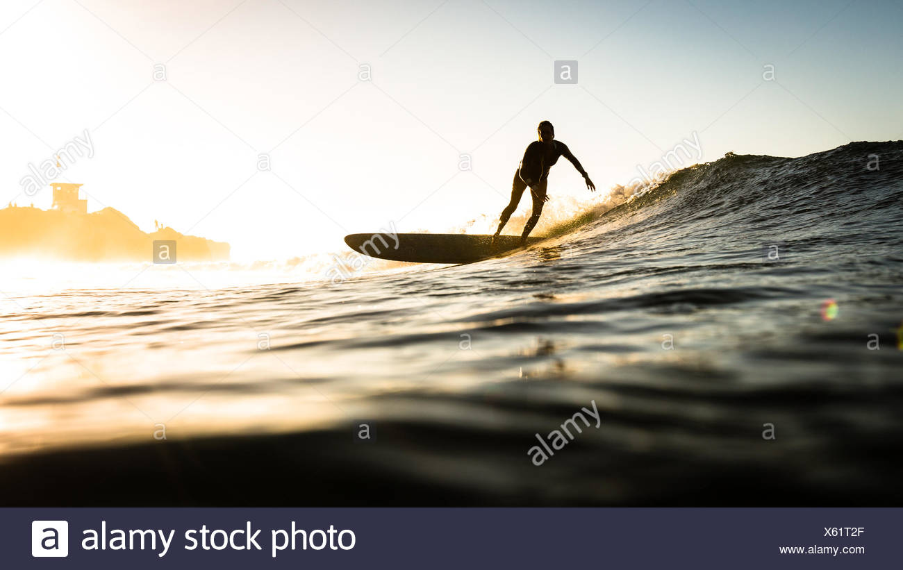 Femme surf au coucher du soleil, Malibu, California, USA Photo Stock