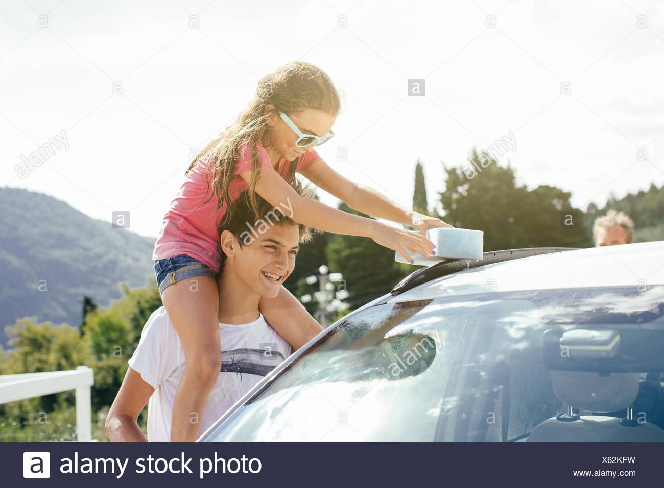 Frère et sœur washing car Photo Stock