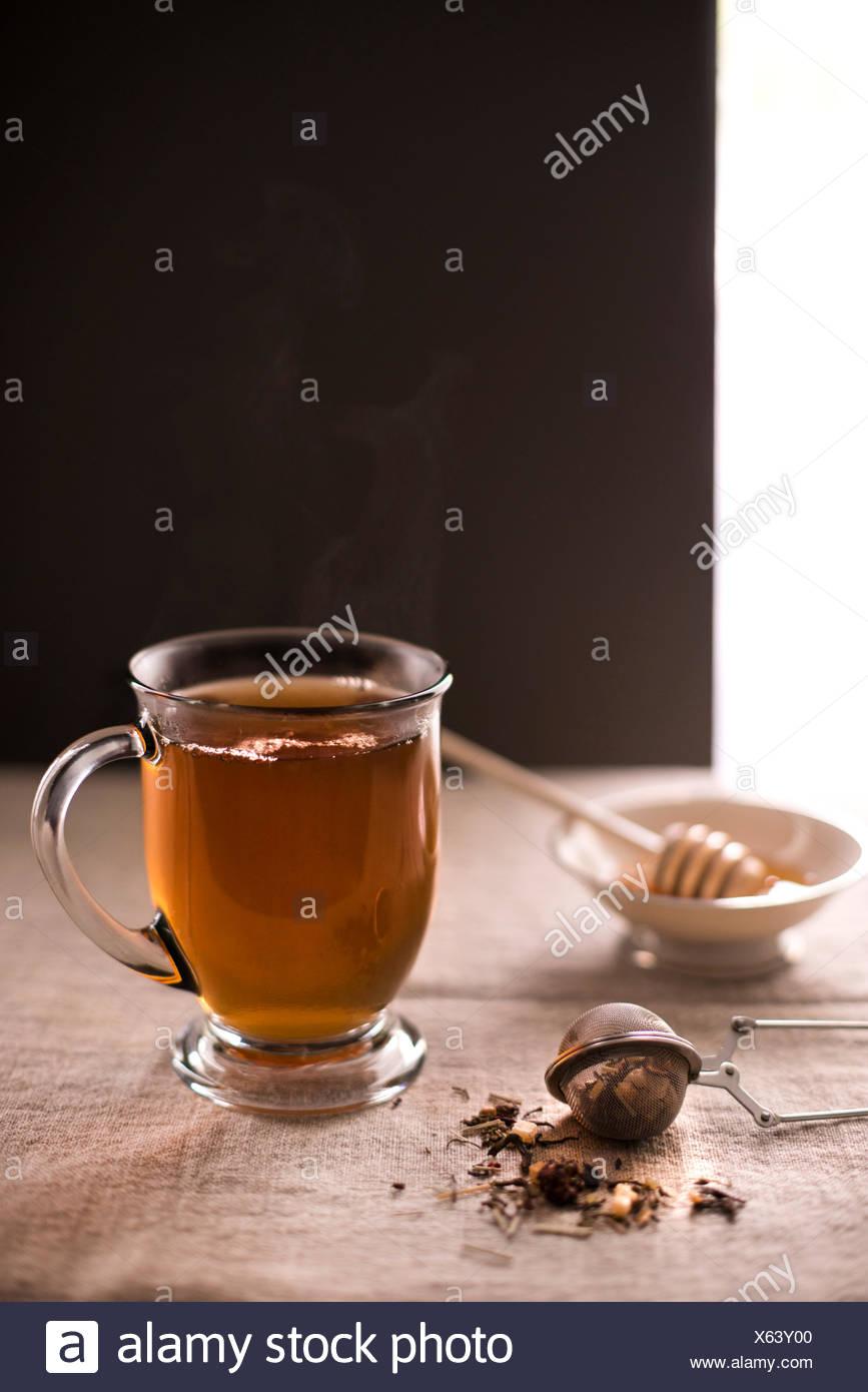 Tasse fumante de thé chaud avec du thé en feuilles en premier plan et le miel avec le balancier dans l'arrière-plan. Linge de maison rustique, surface. Photo Stock