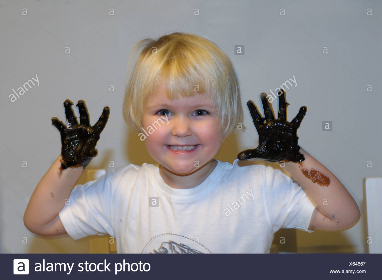 Close-up portrait of smiling girl avec la peinture noire sur ses mains Photo Stock