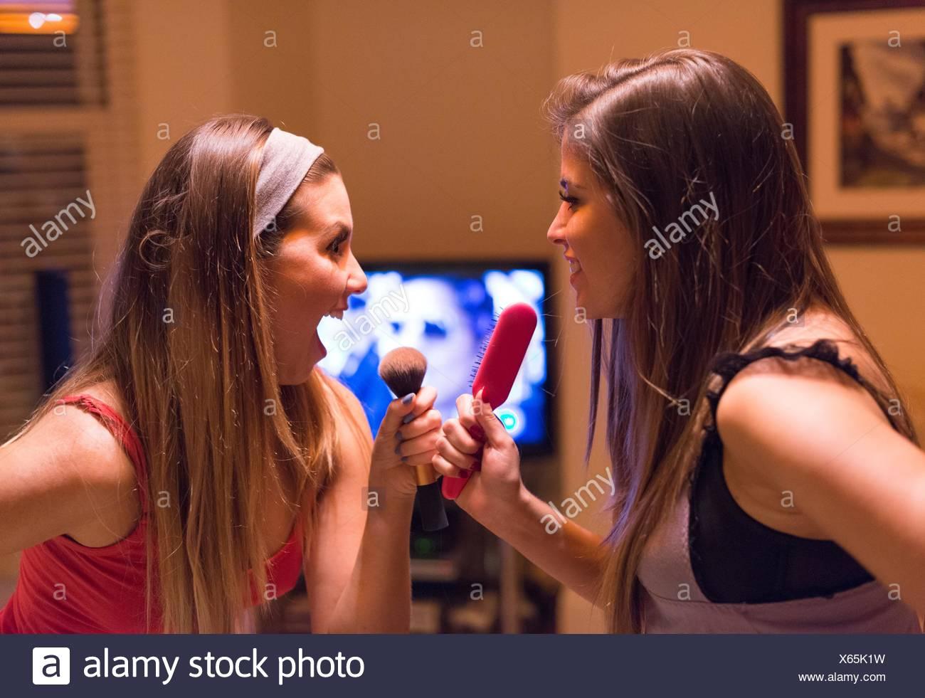 Deux jeunes femmes, chantant en coiffure et maquillage pinceaux Photo Stock