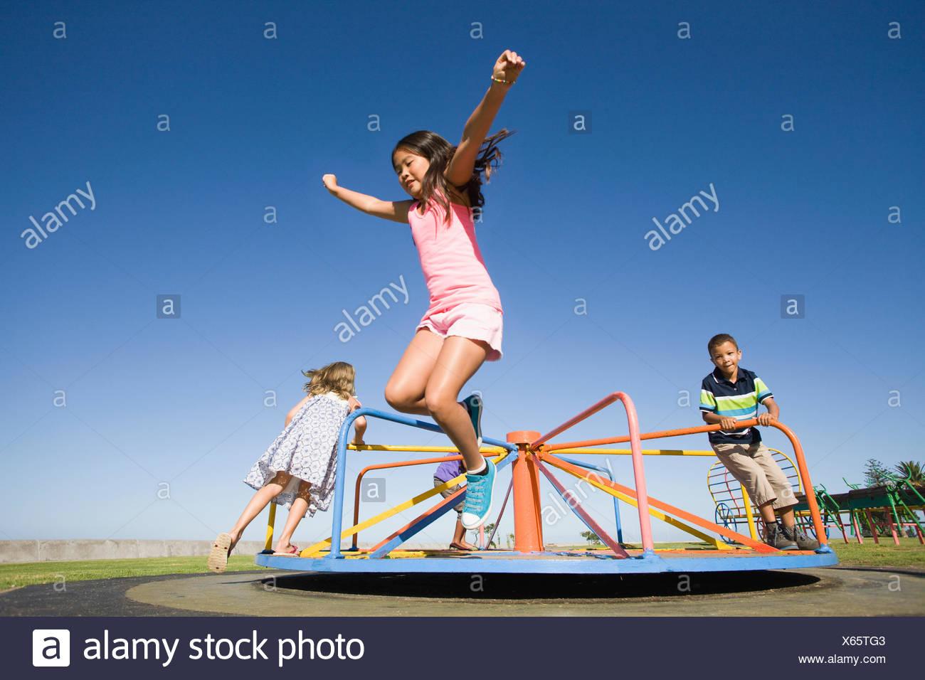 Les enfants sautant hors manège à jeux pour enfants Photo Stock