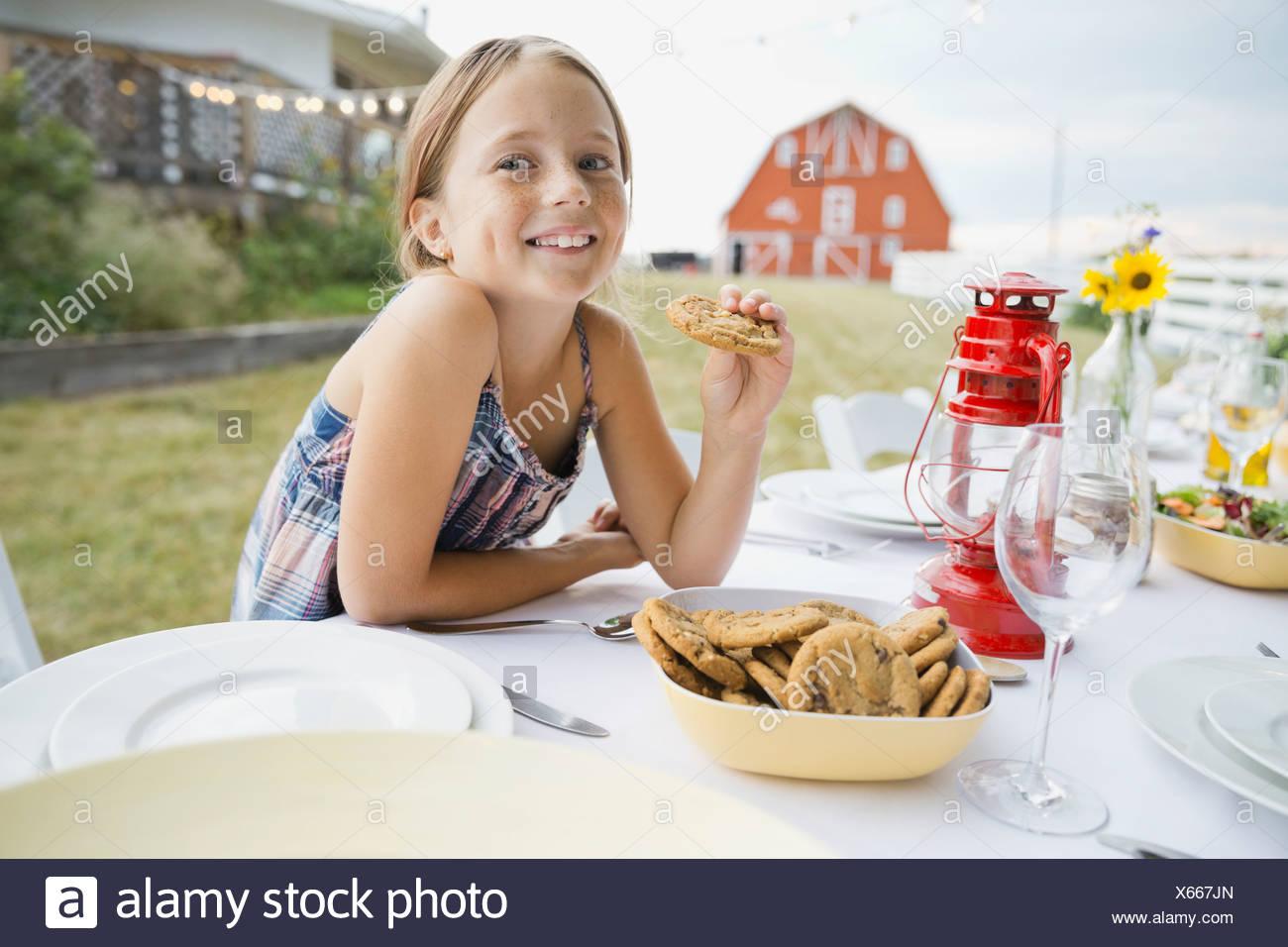 Girl holding cookie à une table de jardin Photo Stock