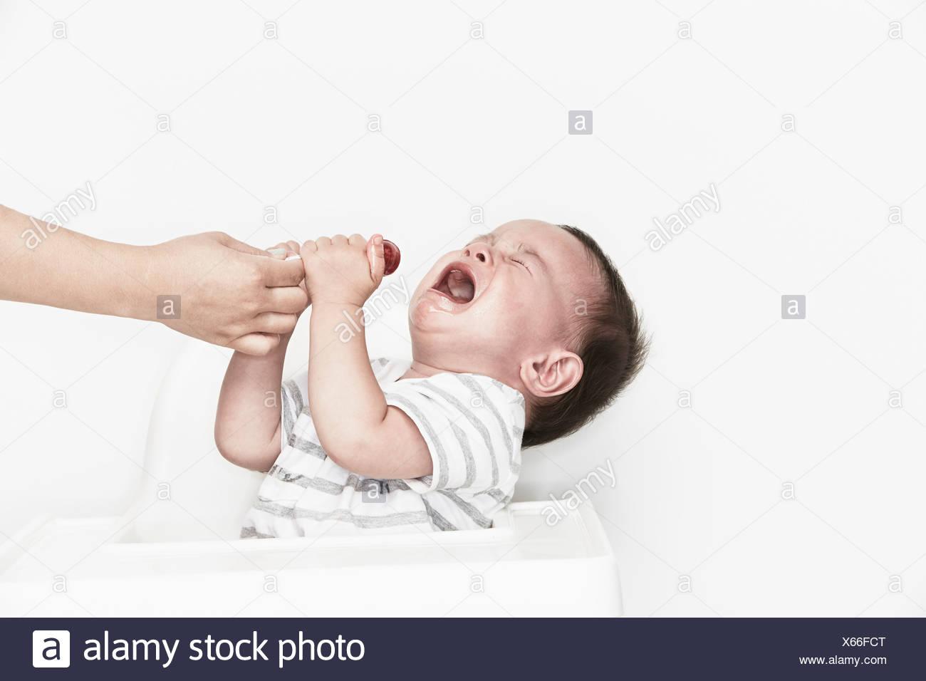 En tenant la main de sucette de bébé qui pleure Photo Stock