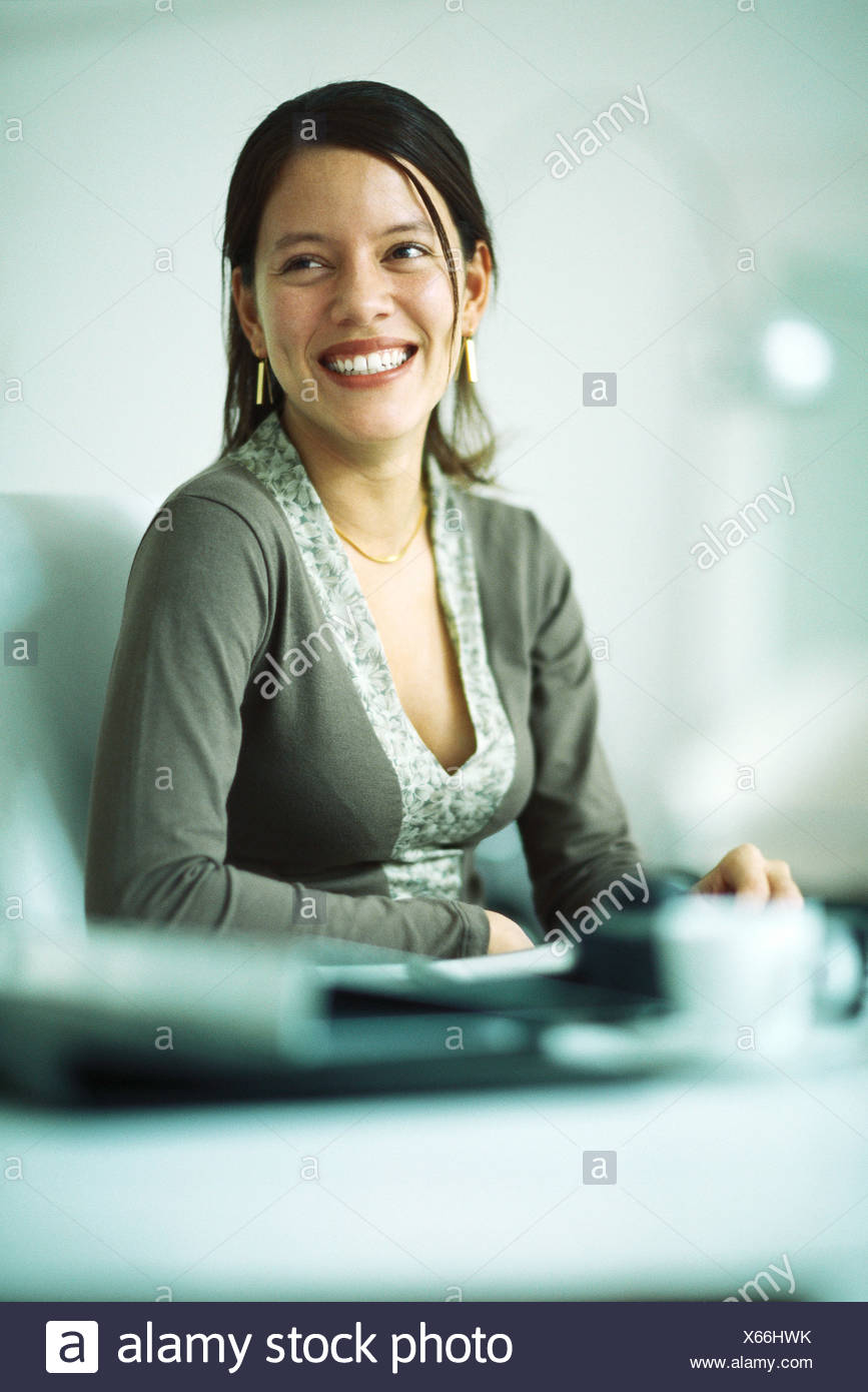 Woman sitting at desk, smiling, Portrait Photo Stock