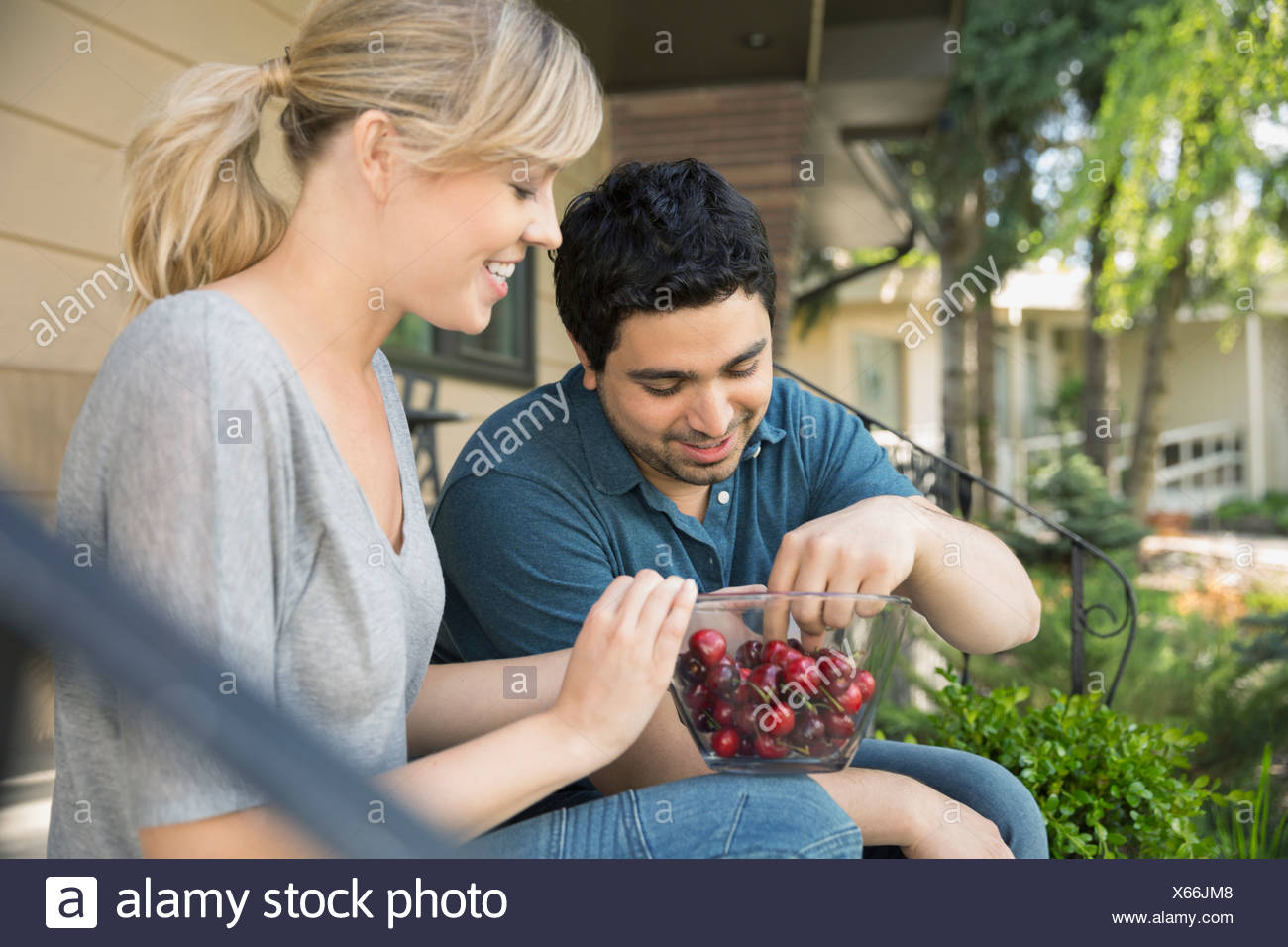 Couple eating cherries sur avant stoop Photo Stock