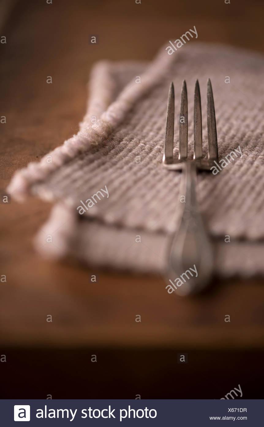 Réglage simple avec un mobilier ancien et d'un napperon vintage de fourche sur une table rustique en bois sombre. Photo Stock
