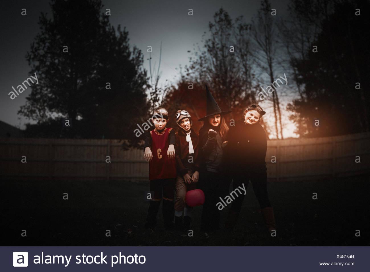 Portrait de garçon et les filles posées dans Halloween costumes in garden at Dusk Photo Stock