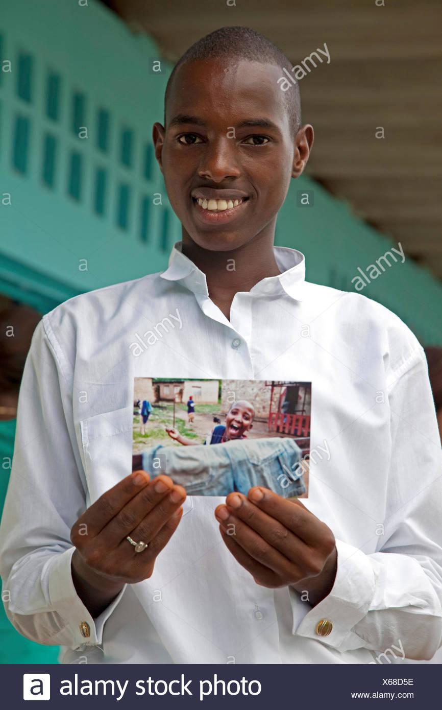 Garçon sourit tout en maintenant une photographie de pair avec lui-même sur elle, BURUNDI, Bujumbura Mairie, Bujumbura Photo Stock