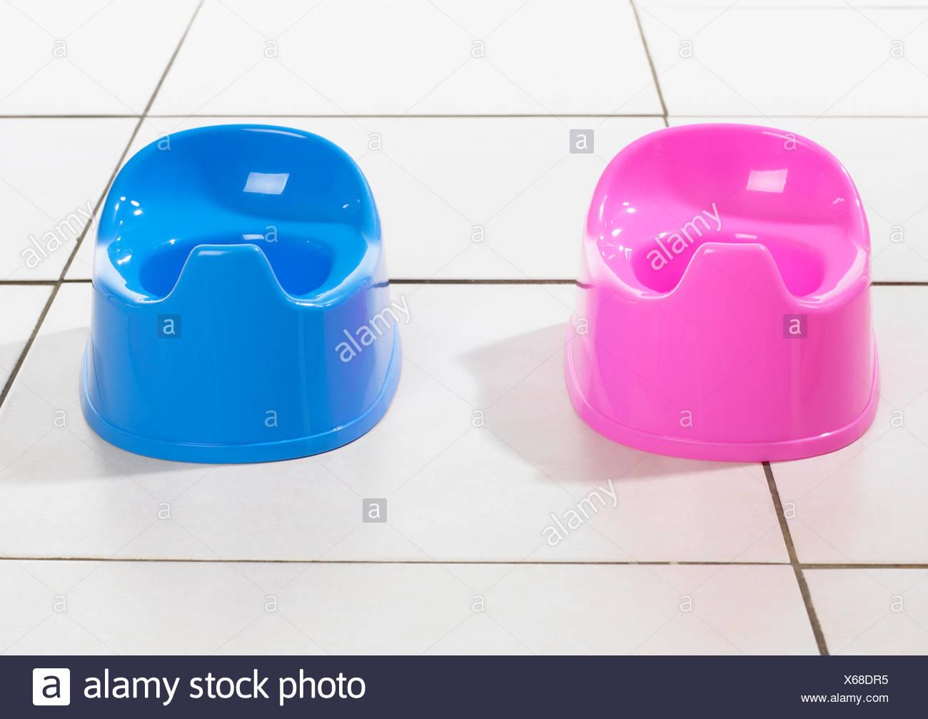 Des pots en plastique pour les filles et les garçons en rose et bleu Photo Stock