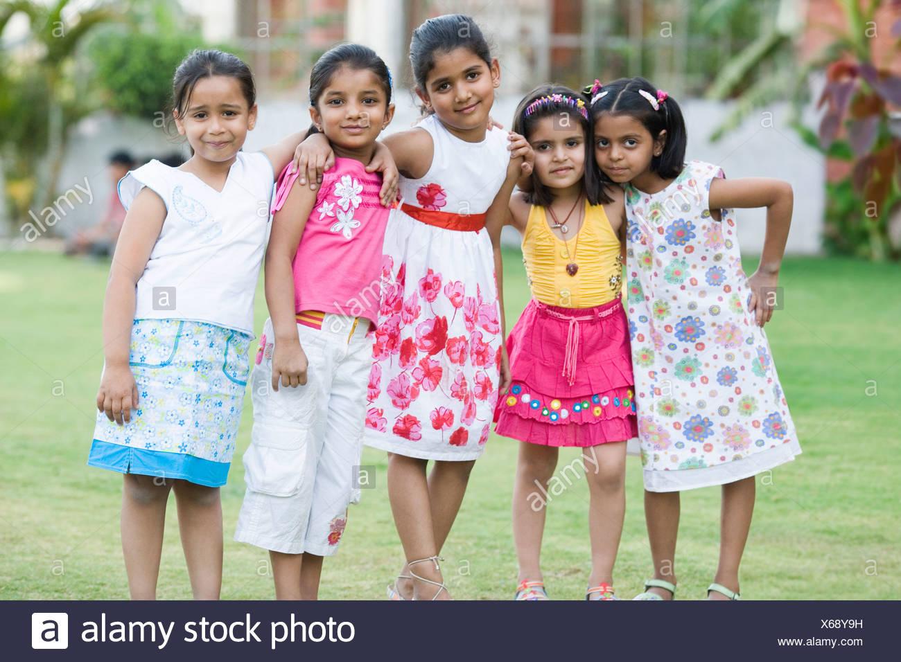 Portrait de cinq filles debout dans une pelouse Photo Stock