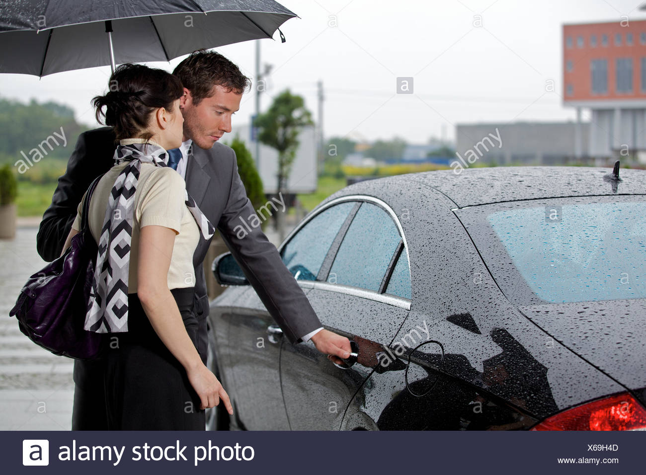 Jeune homme de l'ouverture de la porte de voiture pour femme Photo Stock