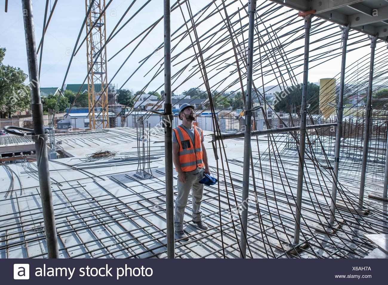 Site manager à la recherche jusqu'à des structures en acier, on construction site Photo Stock