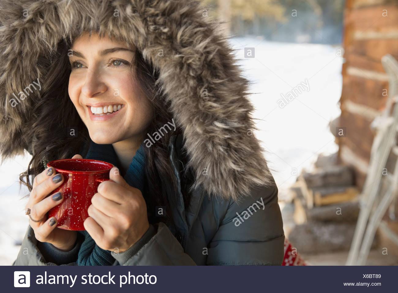 Portrait of woman in fur hood de boire du café en plein air Photo Stock