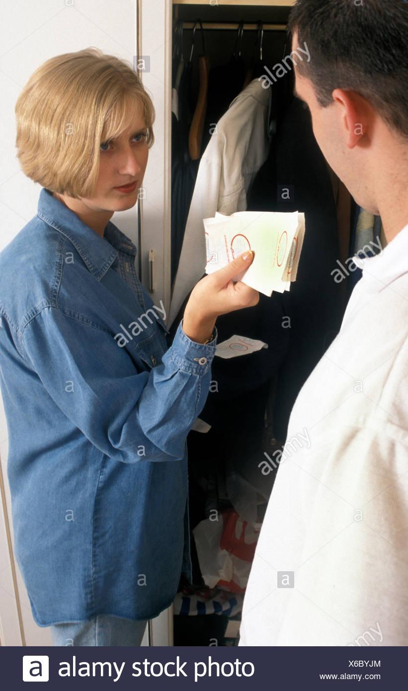 Femme mari confronte comme elle le trouve reçus suspect caché dans ses poches Photo Stock