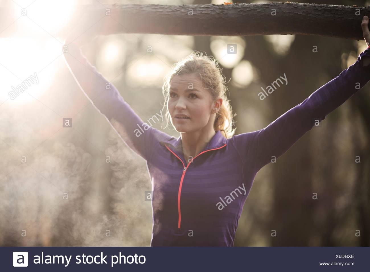 Jeune femme dans les bras levés tenant branche d'arbre, à l'écart, la condensation de souffle Photo Stock