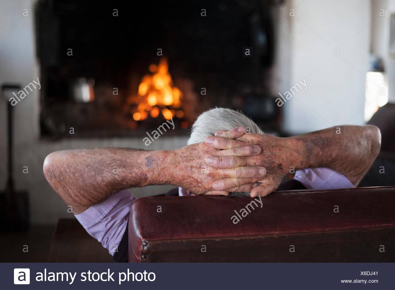 Vue arrière du senior à la maison avec les mains derrière sa tête en face de feu Photo Stock