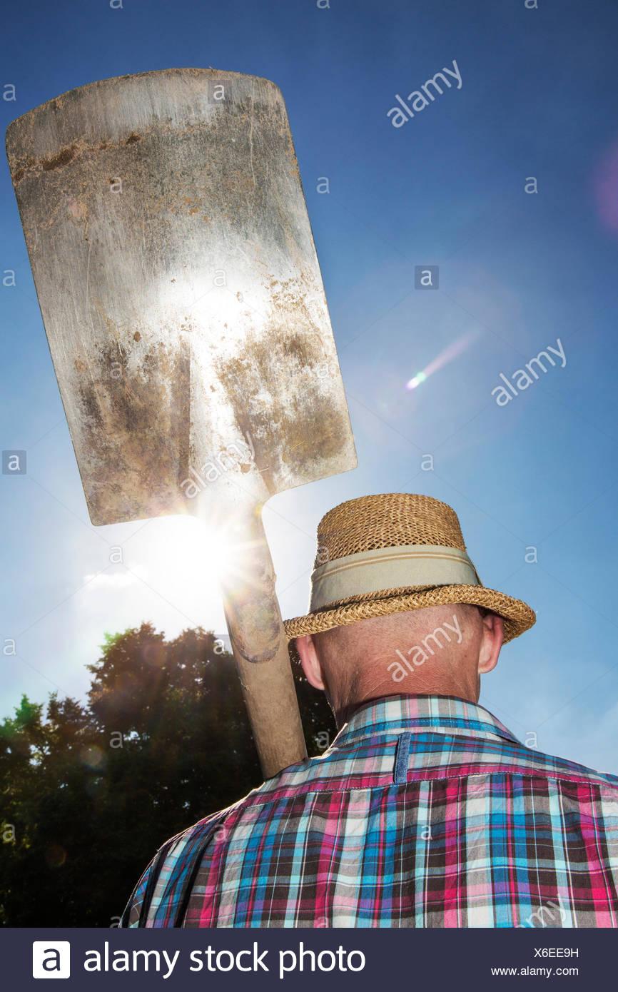 Vue arrière de l'adjudication est jardinier bêche sur son épaule Photo Stock