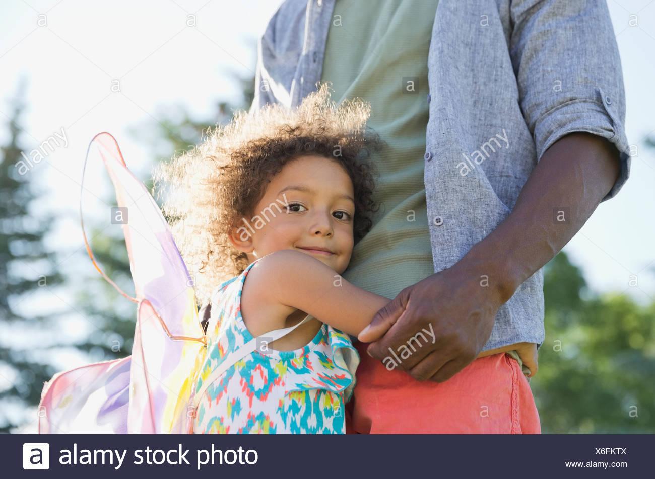 Portrait of cute girl embracing père at park Photo Stock