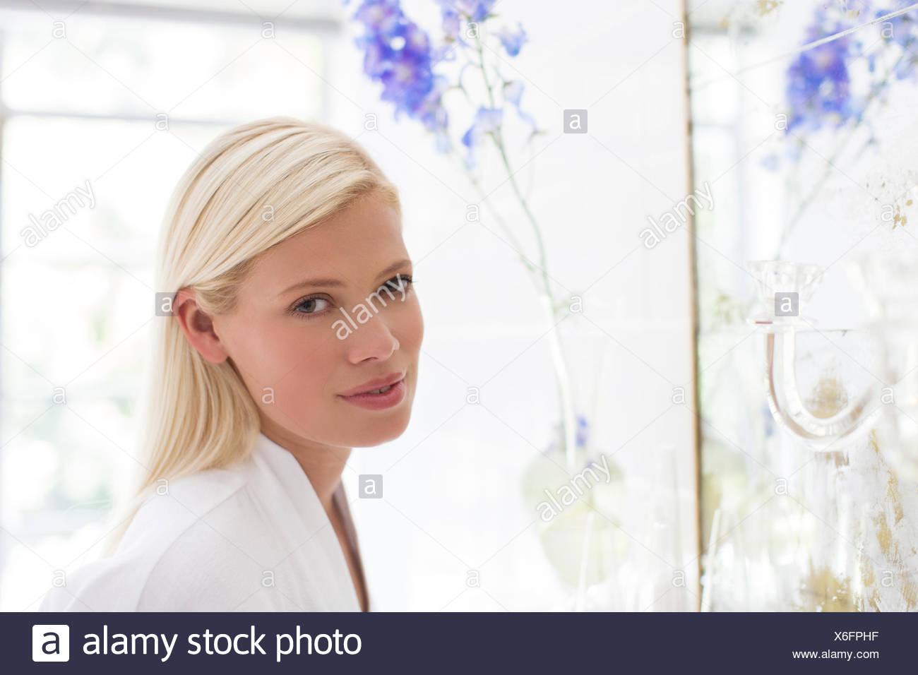 Femme debout au miroir de salle de bains Photo Stock
