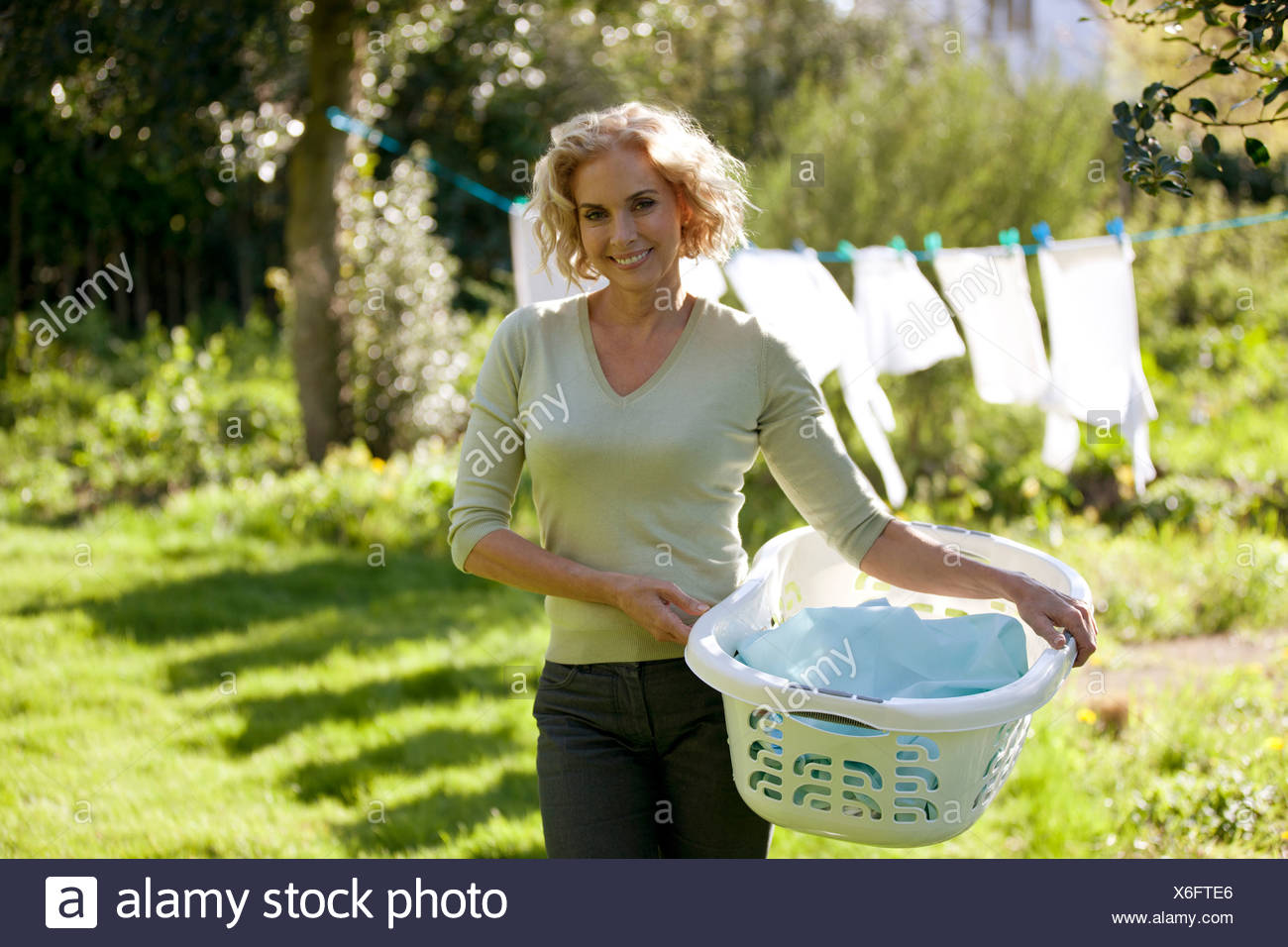 A young woman standing in front of a tenant un panier de blanchisserie Photo Stock