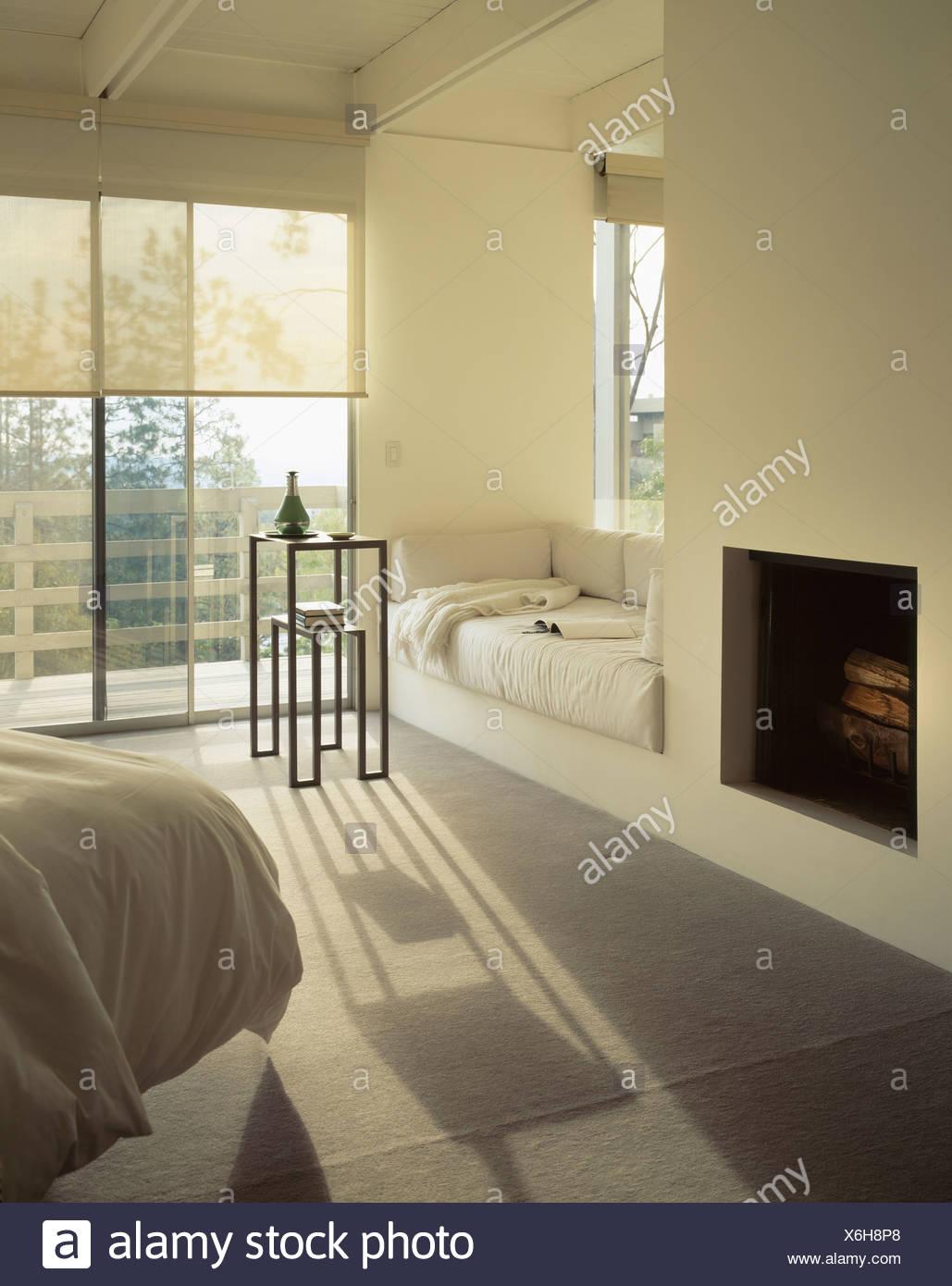 Cheminée Et Fenêtre Fauteuil Avec Coussins En Blanc Crème Moderne Chambre  Avec Moquette Grise Et Portes Fenêtres Avec Stores Crème