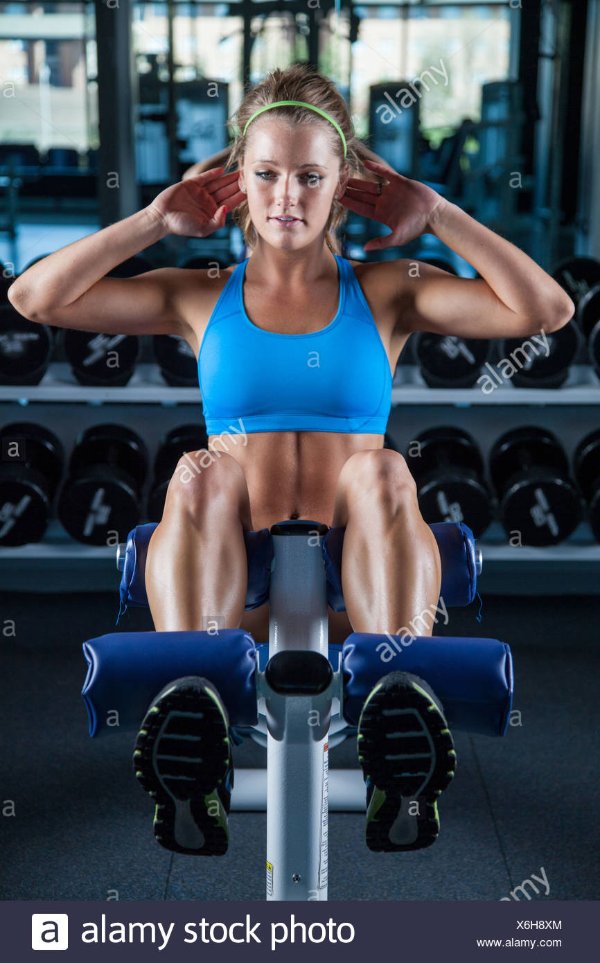 Young woman doing sit ups in gym Photo Stock