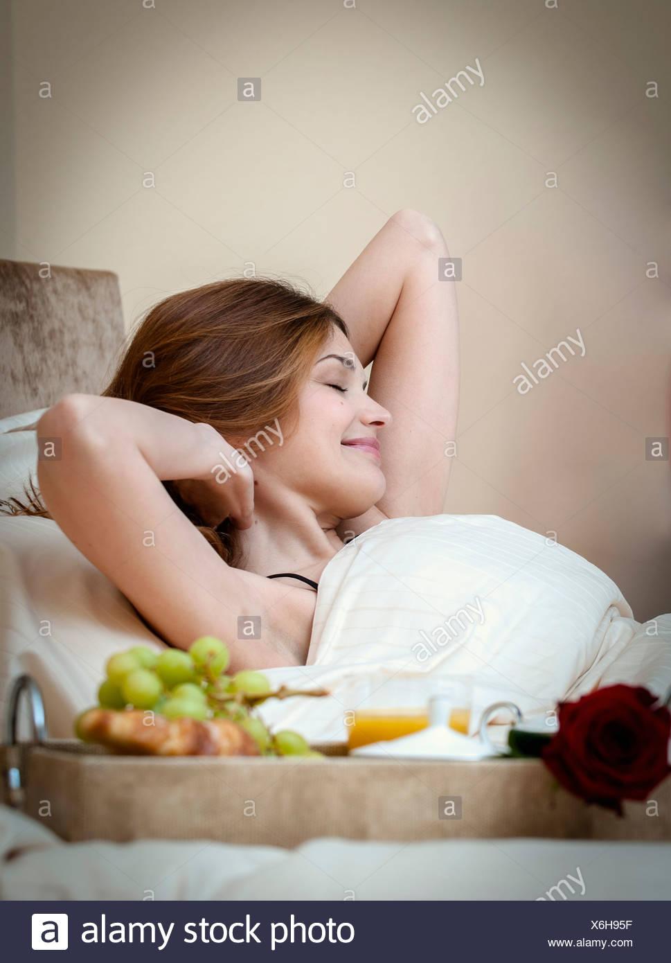 Femme Au Reveil femme un réveil au petit déjeuner au lit banque d'images, photo