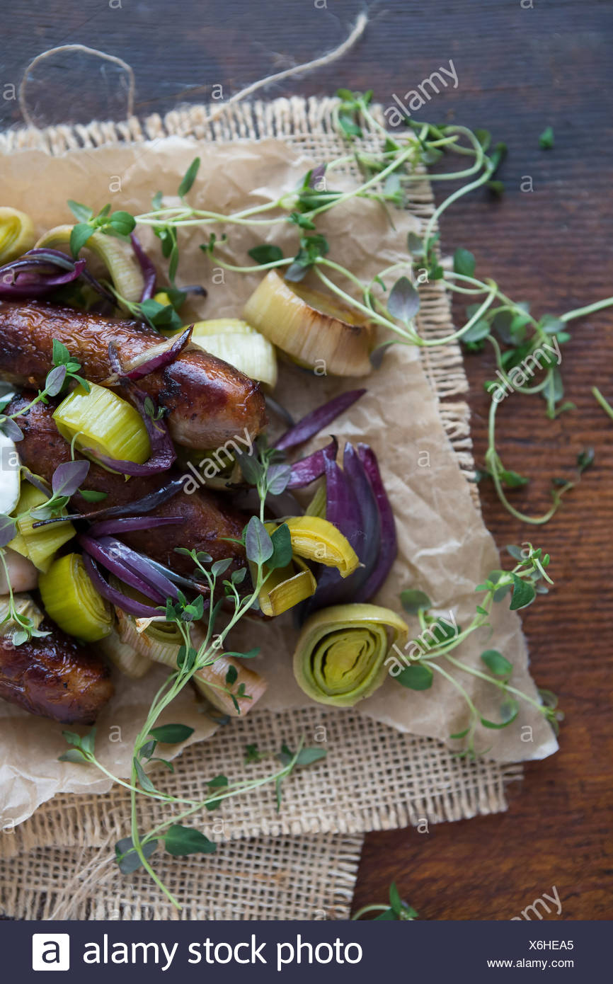 Saucisse, le poireau, l'oignon rouge et le thym sur le papier parchemin Photo Stock