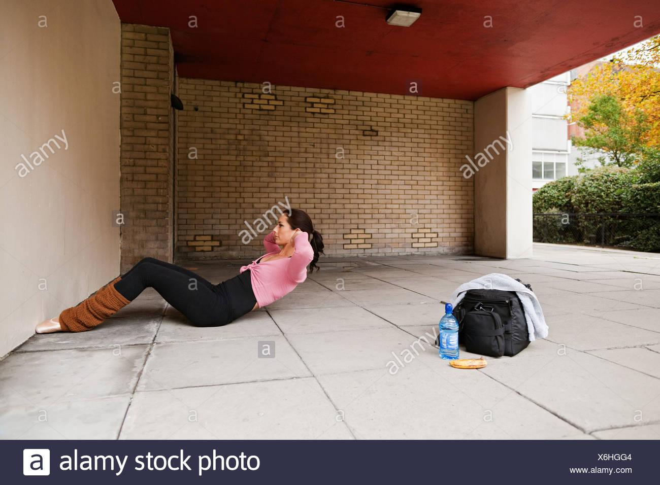 Femme en poignées en exécution d'abdominaux Photo Stock