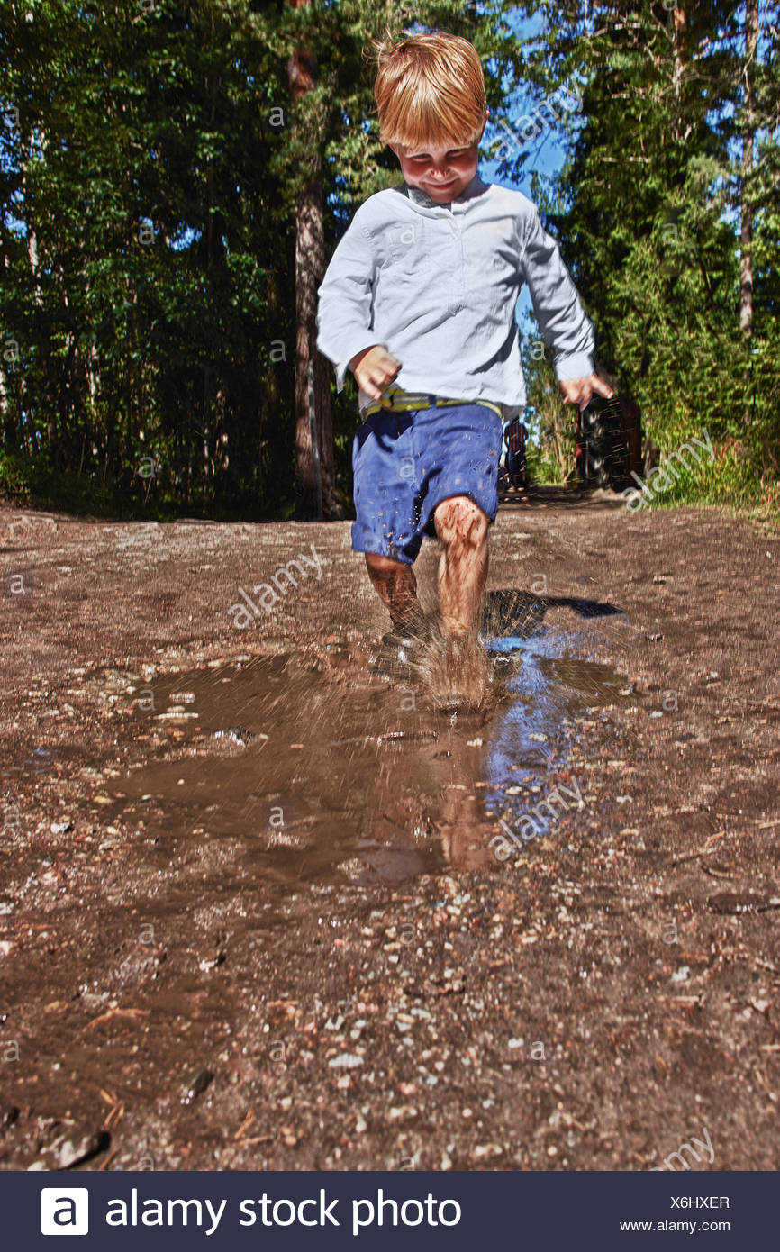 Jeune garçon en éclaboussures flaque boueuse Banque D'Images